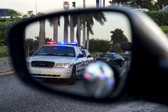 Police on rear view mirror. Patrol cars with their lights on reflected on a rear view mirror Royalty Free Stock Photo