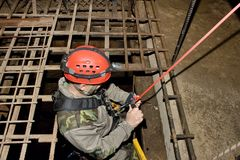 Police rescue worker runs the rope. Into the flooded old mine royalty free stock photos