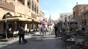 Police riding arabian horses. Doha, Qatar - February 20, 2019: two police officers riding white Arabian horses at Souq Waqif. Fanar Islamic Cultural Center with stock video footage