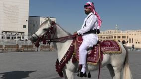 Police riding in Doha center. Doha, Qatar - February 20, 2019: police officer in traditional 1940s Qatari uniform riding white Arabian Horses at square of Souq stock video footage