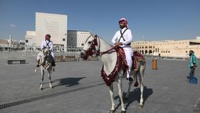 Police riding in Souq Waquif. Doha, Qatar - February 20, 2019: two heritage Police Officers in traditional Qatari uniform riding white Arabian Horses at square stock video footage