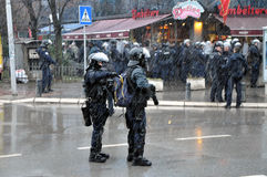 Police in riot gear holding weapon Stock Images