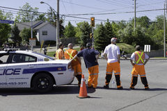 Police and security crew in the middle of the road watching coming city parade. Police car blocking the road intersection and security crew dressed in orange stock photo