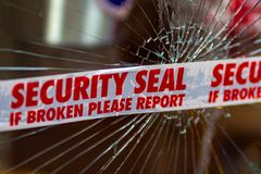 Police Security Seal tape across broken glass window royalty free stock photo