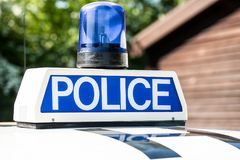 Police sign and blue light on patrol vehicle. Close up of POLICE sign with blue light on the roof of a police patrol vehicle royalty free stock images