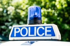Police sign and blue light on patrol vehicle. Close up of POLICE sign with blue light on the roof of a police patrol vehicle stock photography