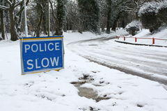 Police Slow Sign. Warning of dangerous driving conditions in winter snow and ice stock image