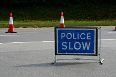 Police slow sign. In the middle of the road stock photo