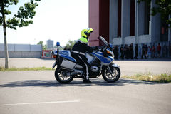 Police at the Soccer Game FSV Mainz 05. Mainz, Germany - August 06, 2016: A policeman on a motorcycle watches fans at the entrance of the Opel Arena at a soccer royalty free stock image