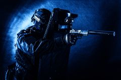 Police special team fighter with pistol and shield. Police special operations team, quick response group fighter in black uniform, helmet and mask aiming with royalty free stock photos