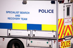 Police Specialist Search and Recovery Van. A white specialist search and recovery police vehicle, with luminous blue, yellow, and orange decal stock photography