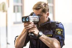 Police with speed enforcement laser. Police officer performing measurement with speed enforcement laser. Stockholm, Sweden royalty free stock photo