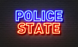 Police state neon sign on brick wall background. Stock Photo