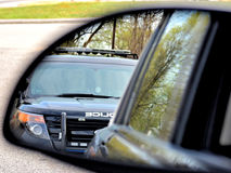 Police Stop. Police patrol car pulling over a motorist as seen in a rear view mirror Royalty Free Stock Photos