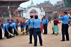 Police Sweeping Street. At Bhaktapur Durbar Square which is one of three Durbar Squares in the Kathmandu Valley in Nepal, all of which are UNESCO World Heritage royalty free stock photography