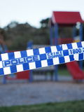Police tape cordoning off an colorful playground area Stock Image