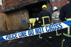 Police tape at fire scene. Firemen at scene of fire cordoned with Police barrier tape stock photo