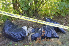 Police Tape and Illegal Garbage Dumping Stock Photos