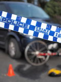Police tape used to cordon off a damaged bicyle under a car and like a crime scene Stock Images