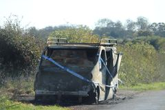 Burnt out van abandoned in a country lane. Police tape wrapped around a burnt out vehicle in a country lane stock images