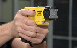 Police Taser gun on aim. Taser X26 ECD (Electronic Control Device) as used by law enforcement officers and armed forces. Taser is classed as a handgun in many stock photo