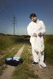 Police technician wearing DNA free suit in fields Royalty Free Stock Photo