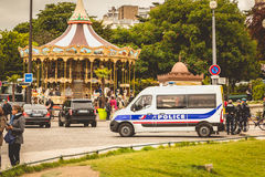 Police truck is parked in the street next to a carousel. PARIS, FRANCE - May 08, 2017 : police truck is parked in the street next to a carousel and there are Stock Images