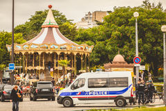 Police truck is parked in the street next to a carousel. PARIS, FRANCE - May 08, 2017 : police truck is parked in the street next to a carousel and there are Stock Photography