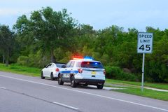 Police truck vehicle pulling over a sports car by speed limit sign. Police truck suv vehicle with flashing red and blue lights has pulled over a sports car for Stock Photography