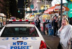 Parked NYPD vehicle seen together with a woman on a phone, seen after an emergency incident. Stock Photos