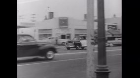 Police vehicles racing through city street, 1950s stock video
