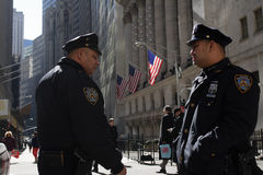 Police And Wall Street. Two Policemen standing in front of New York Stock Exchange building with national flags flying behind Royalty Free Stock Images