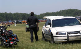 Police Watching. Police keep an eye on parking area at event royalty free stock image
