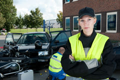 Police Woman. Posing on the site of a car crash, with a paramedic working in the background Stock Photo