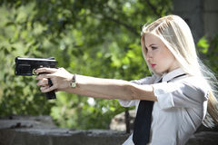 Police woman aiming with handgun in blouse and tie Royalty Free Stock Photography