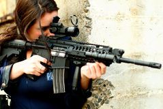 Police woman with assault gun. A police woman aiming an assault rifle Stock Photography