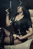 Police woman with gun. Seductive police woman with gun sitting in an arm chair Royalty Free Stock Photos