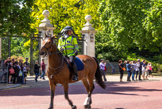 Police woman on horseback on  The Mall, street in front of Buckingham Palace in London. Unidentified tourists and police woman on horseback on  The Mall, street Stock Image