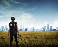 Police woman looking the city in the middle of field Royalty Free Stock Images