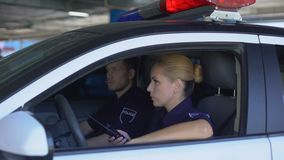 Police woman receiving call on car radio and rushing to accident place with mate. Stock footage stock video footage