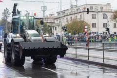 Police workers are riding backhoe loader on military parade. European street, Prague-October 28, 2018: Police workers are riding backhoe loader on military royalty free stock photos