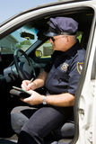 Police - Writing Citation. Police officer sitting in his squad car writing a citation Royalty Free Stock Images