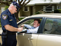 Police - Writing Ticket. Police officer writing a traffic citation while an unfortunate driver looks on from his car Stock Photos
