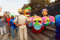 Policeman accompanies procession with figures of defeated terrorists during the traditional Goa carnival Stock Photography