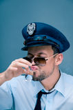 Policeman addicted to alcohol Royalty Free Stock Images