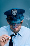 Policeman addicted to cigarettes Stock Image