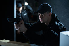 Policeman aiming gun during action. Portrait of an attractive policeman aiming gun during action stock photos