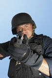 Policeman Aiming Gun Against Blue Sky Stock Images