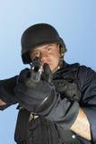 Policeman Aiming Gun Against Blue Sky Stock Images