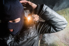 Policeman aiming pistol towards busted masked gangster at night. Policeman Aiming Pistol Towards Busted Gangster stock photos